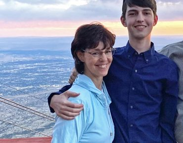 Nate Taylor on the right with his arm around his mom, Bridget McCandless, posing for a photo with a view of the city from a high elevation